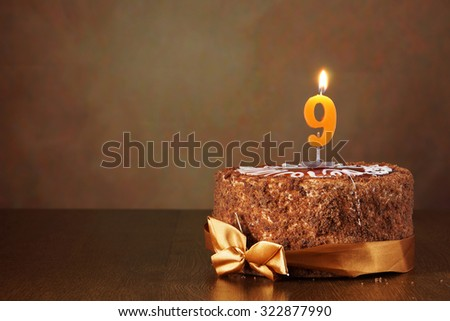 Birthday chocolate cake with burning candle as a number nine on brown background - stock photo