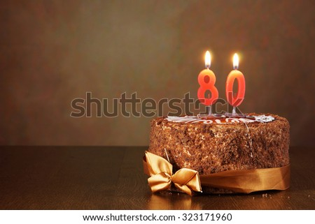 Birthday chocolate cake with burning candles as a number eighty on brown background