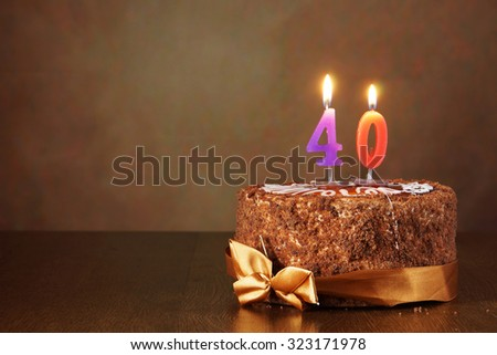 Birthday chocolate cake with burning candles as a number forty on brown background