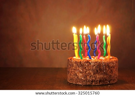 Birthday chocolate cake with burning candles on brown background - stock photo