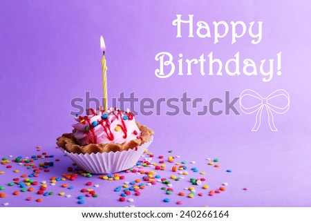 Birthday cup cake with candle and colorful sparkles on purple background - stock photo