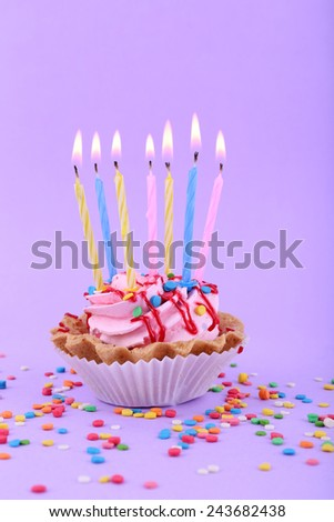 Birthday cup cake with candles and colorful sparkles on purple background - stock photo