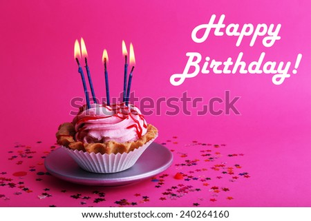 Birthday cup cake with candles and colorful stars on pink background - stock photo