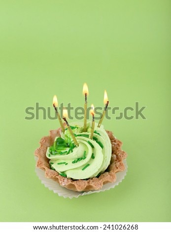 Birthday cup cake with candles on green background - stock photo