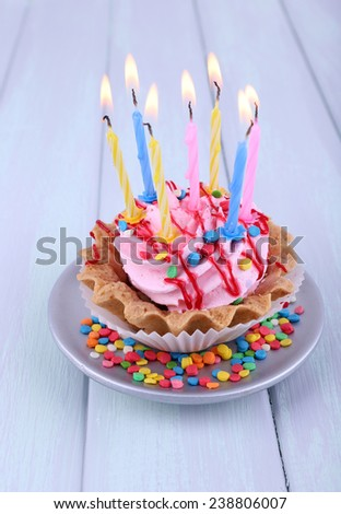 Birthday cup cake with candles on saucer and sparkles on color wooden background