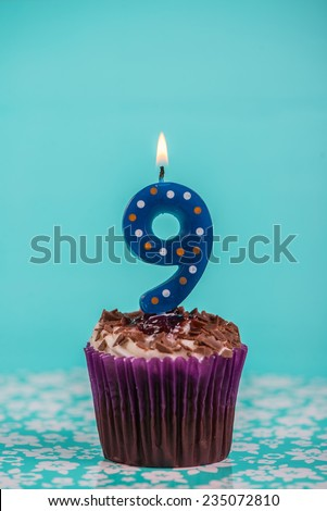 birthday cup cake with number nine candle on blue background - stock photo