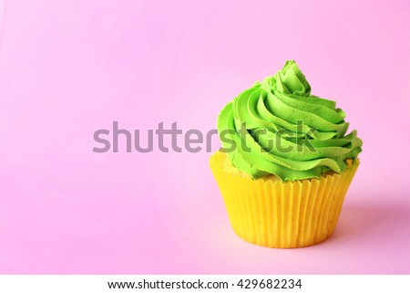 Birthday cupcake on light pink background