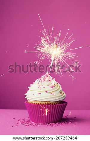 Birthday cupcake with a sparkler against a pink background - stock photo