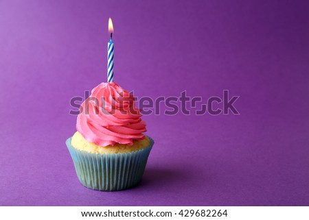Birthday cupcake with candle on purple background