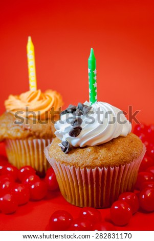 Birthday cupcake with candle on top and candies with red background