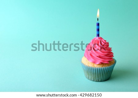 Birthday cupcake with candle on turquoise background - stock photo