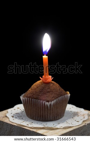 Birthday cupcake with candle over black