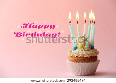 Birthday cupcake with candles on color background - stock photo