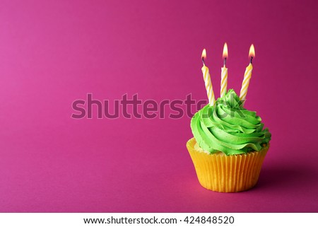 Birthday cupcake with candles on pink background - stock photo