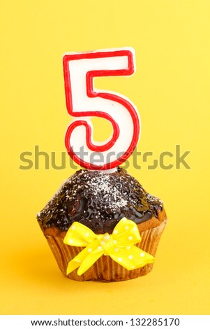 Birthday cupcake with chocolate frosting on yellow background - stock photo