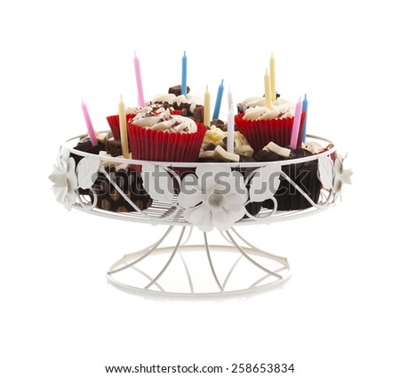 Birthday cupcakes on a stand with candles on a white background - stock photo