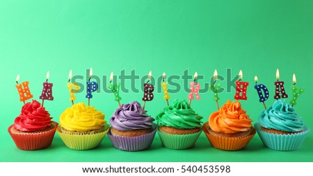 Birthday cupcakes with candles on color background