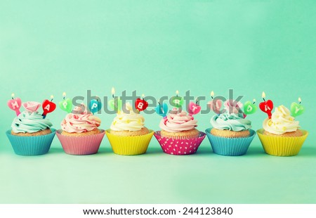 Birthday cupcakes with candles on green background