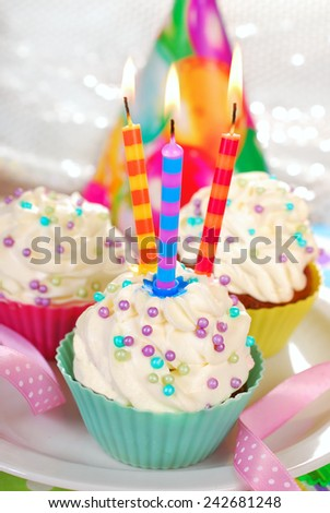 birthday cupcakes with sugar sprinkles and three candles on festive table