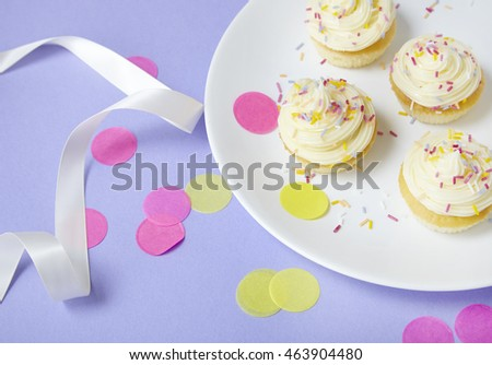 Birthday cupcakes with vanilla frosting and sprinkles on a purple background with confetti and a ribbon