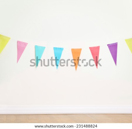 Birthday decoration flags on a plain white wall shot with tilt and shift lens - stock photo