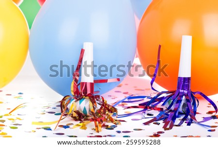 Birthday decorations of noisemakers and balloons - stock photo