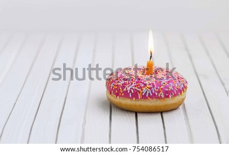Birthday donut with pink glaze and colorful candies and burning candle , birthday concept