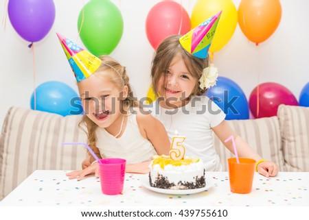 Birthday girl and her friend enjoying birthday party - stock photo