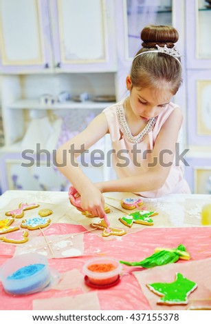 birthday girl decorating cookies at birthday party - stock photo