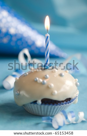 Birthday muffin with blue candle on blue background - stock photo
