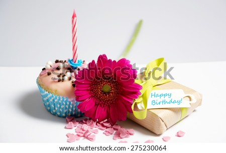birthday muffin with flower and present - stock photo