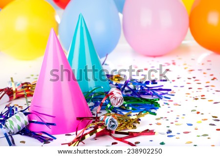 Birthday party decorations of hats, noisemakers, confetti and balloons - stock photo