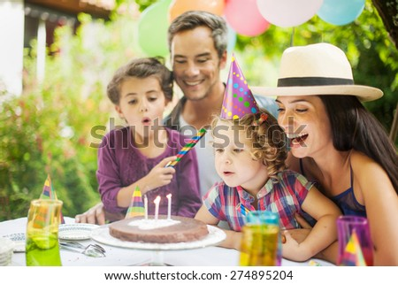Birthday party in family. Girl blowing candles for her three years old - stock photo