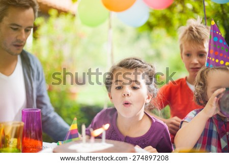 Birthday party in family. Girl blowing candles with her siblings - stock photo