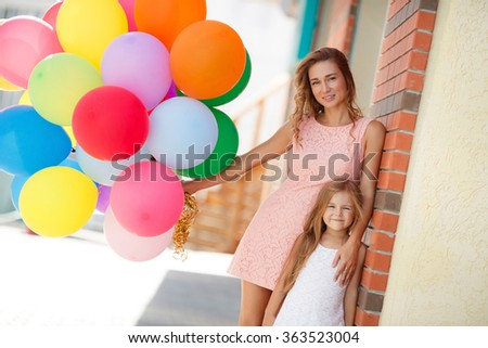 Birthday party of baby girl, cheerful little child with mother having fun outdoors with many colorful balloons, happy family life. summer holidays, celebration, mother and child with colorful balloons