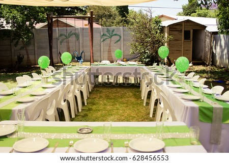 Birthday Party Table Setup With Green Balloons And Decor Outdoors In Yard
