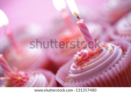 Birthday pink cupcakes with burning candles - stock photo