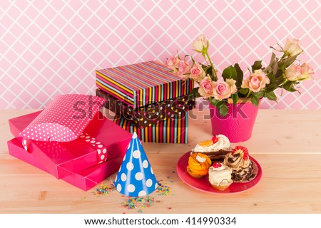 Birthday presents flowers and fancy cakes - stock photo