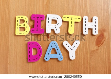 BIRTHDAY, spell by woody puzzle letters with woody background - stock photo