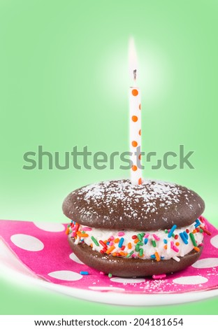Birthday Whoopie pie with a candle, decorated with sprinkles and sugar. Light green background, shallow depth of field.