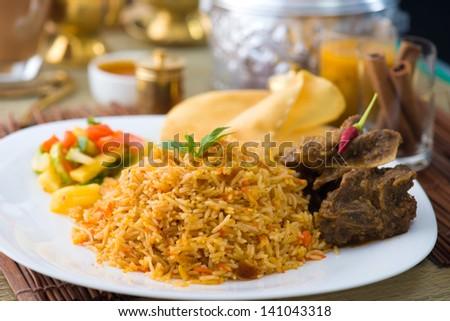 Biryani basmati mutton rice with traditional items on background - stock photo