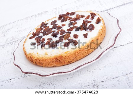 Biscuit cake with whipped cream and concentrated milk, raisins on a white wooden background