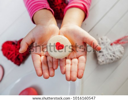 Biscuit macarons with heart shape in child hands, giving and sharing love concept
