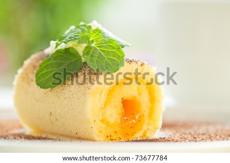 Biscuit roll with cream and mint as outdoor photo - stock photo