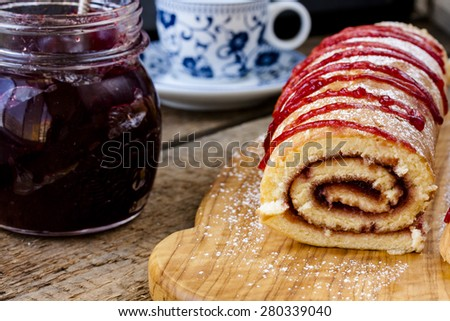Biscuit roulade with cherry jam on a background of wooden boards - stock photo