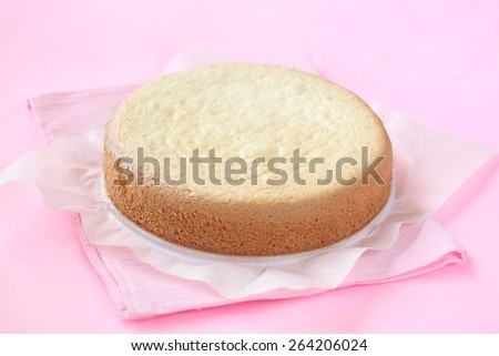 Biscuit Sponge Cake on a baking paper, on a light pink background. - stock photo