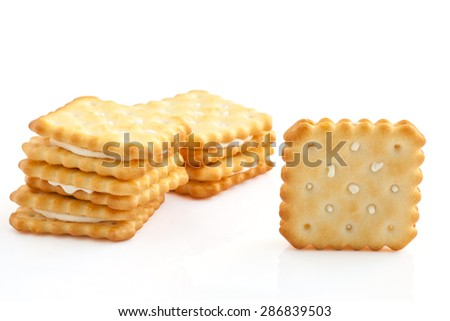 BISCUITS - A stack of square biscuits puff sandwich lemon flavoured cream isolated on white