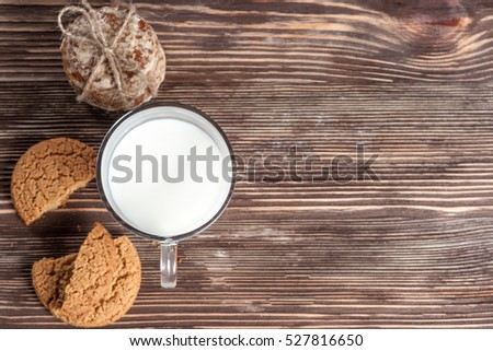 biscuits and cup of milk on old wooden table