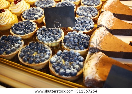 Biscuits and sweets on sale in pastry shop. Blank price tag - stock photo