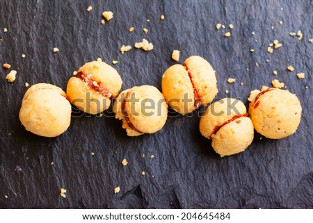 "Biscuits ""Baci di dama"" in a row over black stone - stock photo"